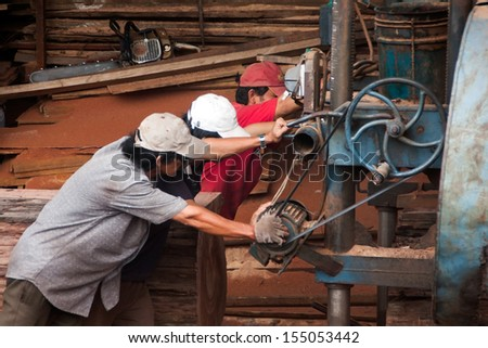 QUY NHON, VIET NAM, JUNE 18: Three woodworker try to pull cumbersome machine to split section of a tree trunk into plank at sawmill. June 18, 2012