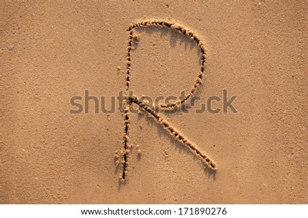 R text written in the sandy on the beach - stock photo