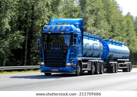 RAASEPORI, FINLAND - AUGUST 17, 2014: Blue Scania tanker truck on the road. At IIA, Scania presents new innovations that provide significant fuel savings. Photo: use of panning, motion blur. - stock photo