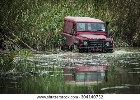 RABAT, MALTA - JANUARY 19, 2014: A 1989 Land Rover Defender wades through deep rain water.  The Defender is one of the most off-road capable vehicles in history. - stock photo