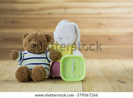 Rabbit and brown bear doll sit on the wood floor as represent lovely family with green clock - stock photo