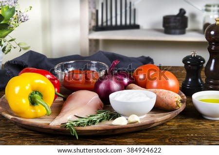 Rabbit or chicken breasts with fresh healthy  vegetables, oil and spices.  Raw products on the wooden background  - stock photo