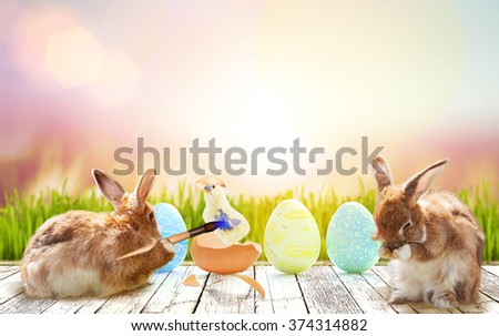 rabbit paint a baby chicken and colorful egg in flare light on Green bokeh background .easter background concept - stock photo
