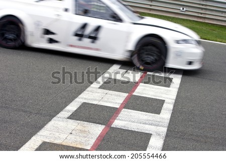 Race car crossing the finish line on a circuit - stock photo