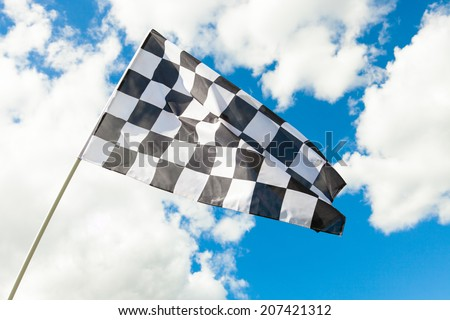 Race flag with blue sky and clouds on background - stock photo