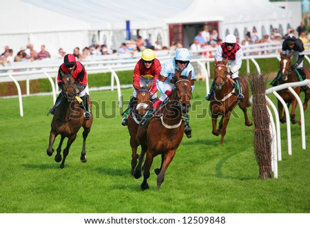 race horses rounding a turn in front of grandstand - stock photo