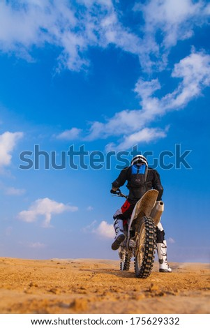racer on a motorcycle in the desert, in the day - stock photo