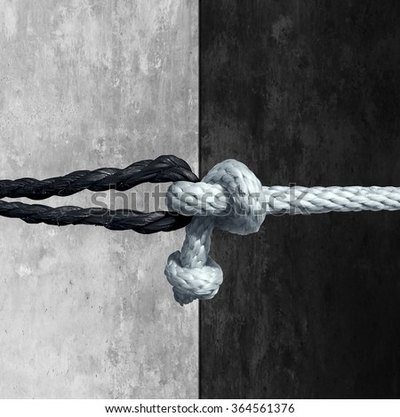Racial unity concept as a symbol against racism in society as a white and black rope tied together as a metaphor for friendship and respect. - stock photo
