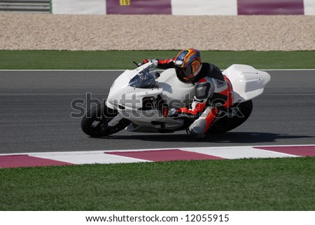 Racing bike rider leaning into a fast corner on track day. - stock photo