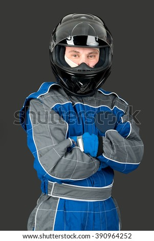 Racing driver posing with helmet isolated in a dark background - stock photo