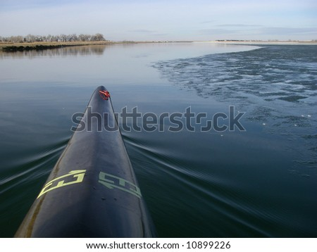 racing kayak with a temporary racing number 13 on a partially frozen calm lake - a paddler perspective