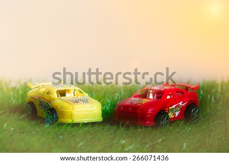 Racing toy car on pastel style grass made with effect light background - stock photo