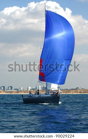 Racing yacht with blue spinnaker - stock photo