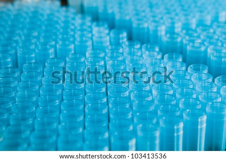 rack of blue plastic pipette nozzles made of polypropylene - stock photo