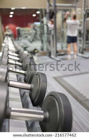 Rack of dumbbells in health club with man lifting weights in background