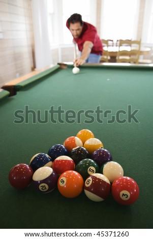 Racked pool balls as a man prepares to break. Vertical shot. - stock photo