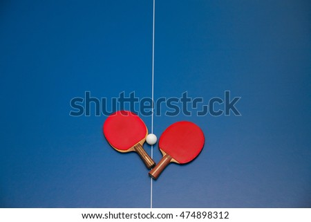 rackets for table tennis of red color and a ball on a tennis table view
