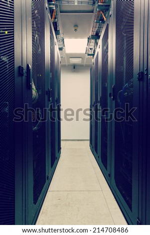 racks in the data center and the corridor between them - stock photo