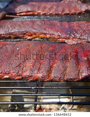 Racks of BBQ ribs on a hot grill - stock photo