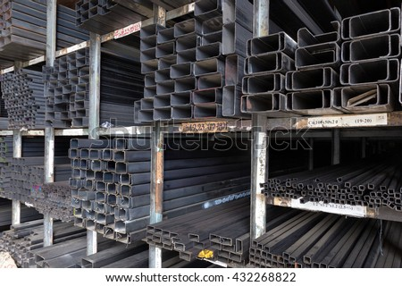Racks of construction steel pipes in rectangle shape, various sizes, thickness, and weight - stock photo