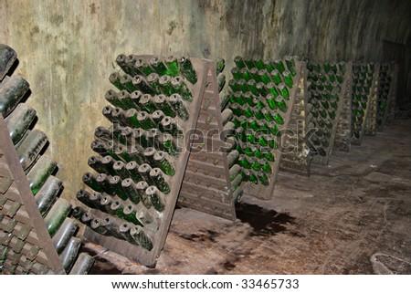 Racks with bottles in a dark wine cellar - stock photo