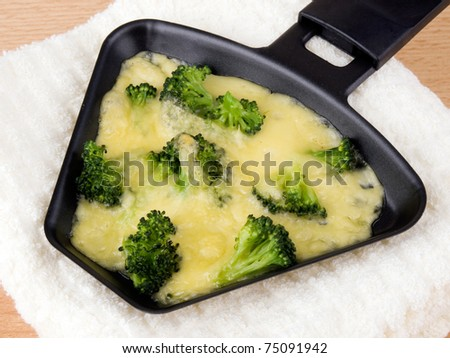 Raclette pan with cheese and broccoli laing on soft napkin - stock photo