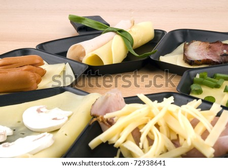 Raclette pans with edam cheese and ham, bacon, mushroom, spring onion, coctail sousages on wooden table - stock photo
