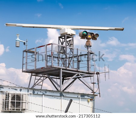 Radar station tower with camera above blue cloudy sky - stock photo