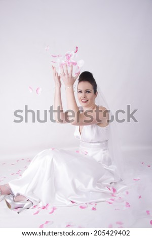 Radiant Bride playing with rose pebbles smiling - stock photo