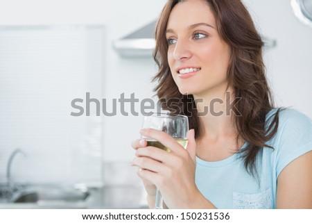 Radiant brunette drinking white wine in her kitchen - stock photo