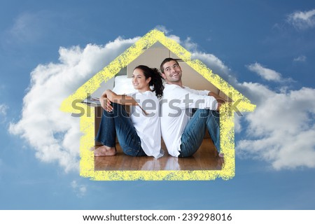 Radiant couple with unpacking boxes moving to a new house against cloudy sky - stock photo