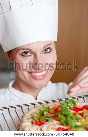 Radiant female chef cooking a pizza in a kitchen - stock photo
