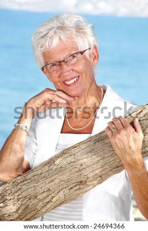 radiant senior lady outdoors - bright lifestyle portrait - stock photo