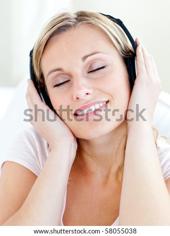Radiant young woman listen to music wearing headphones in the living room - stock photo
