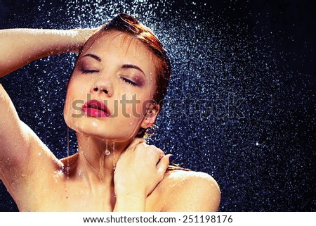Radiantly gorgeous. Portrait of beautiful  young woman taking a shower while standing against black background - stock photo