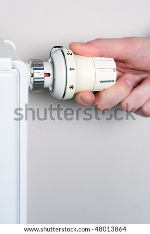 Radiator adjustment. Man's hand adjusting radiator temperature. - stock photo