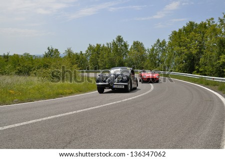 RADICOFANI (SI) ITALY - MAY 19: A red Maserati 150S overtakes a black Jaguar XK 120 during the 1000 Miglia 2012, on May 19, 2012 in Radicofani (SI) - stock photo