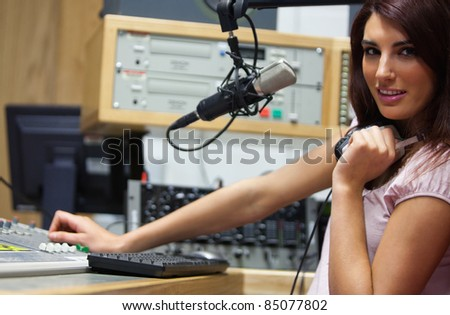 Radio host setting the sound while looking at the camera - stock photo