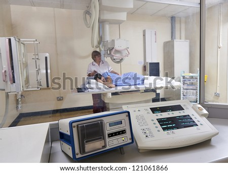 radiographer preparing male teenage patient for an X Ray viewed from control room showing equipment - stock photo