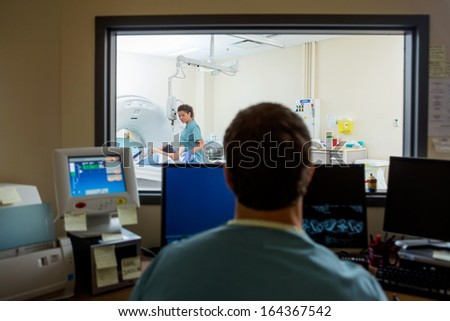 Radiologist operating computers in CT scan lab - stock photo