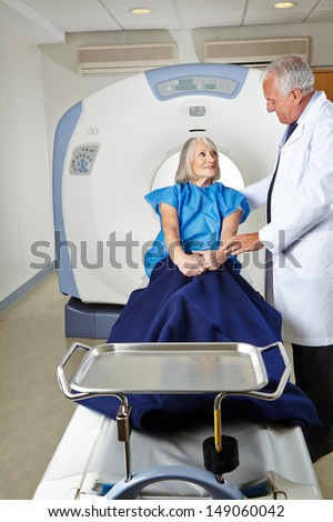 Radiologist talking to a senior woman patient at MRI therapy - stock photo