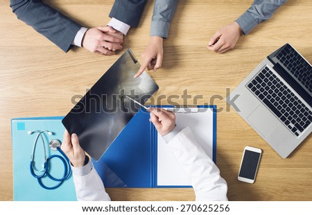 Radiologist working at his desk checking a patient's x-ray and pointing with a pen, top view unrecognizable people - stock photo
