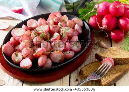 Radish fried in oil on a cast-iron frying pan - stock photo