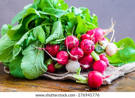 Radishes on rustic background.Organic farm vegetables. - stock photo