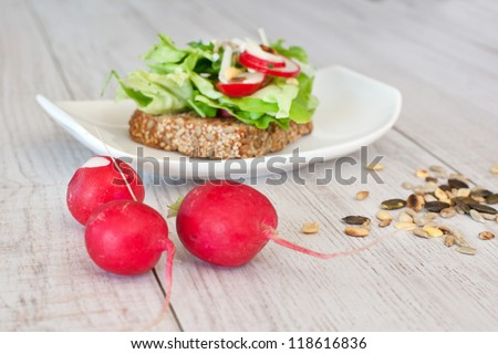 Radishes with healthy sandwich with salad, radish and pumpkin seeds on background with focus on radish - stock photo