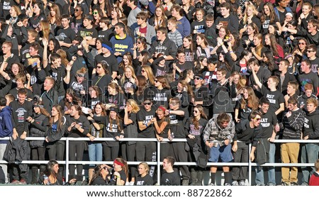 RADNOR, PA - NOVEMBER 12: The Lower Merion fan section cheer a late touchdown by the aces during the 115th meeting of Radnor and Lower Merion High School football teams November 12, 2011 in Radnor, PA - stock photo