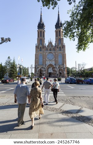 RADOM CITY, POLAND - August 8, 2014: Unidentified people walk in front of Catholic cathedral of the Protection of the Blessed Virgin Mary in Radom, Poland - stock photo