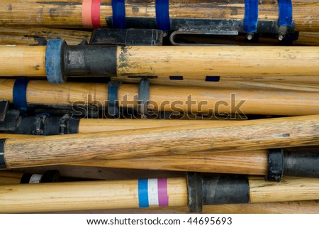 Raft oars piled up after a rafting trip through the Grand Canyon - stock photo