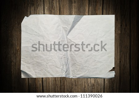Ragged paper sheet on a wooden background - stock photo