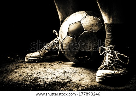 Ragged sneakers with a soccer ball - stock photo